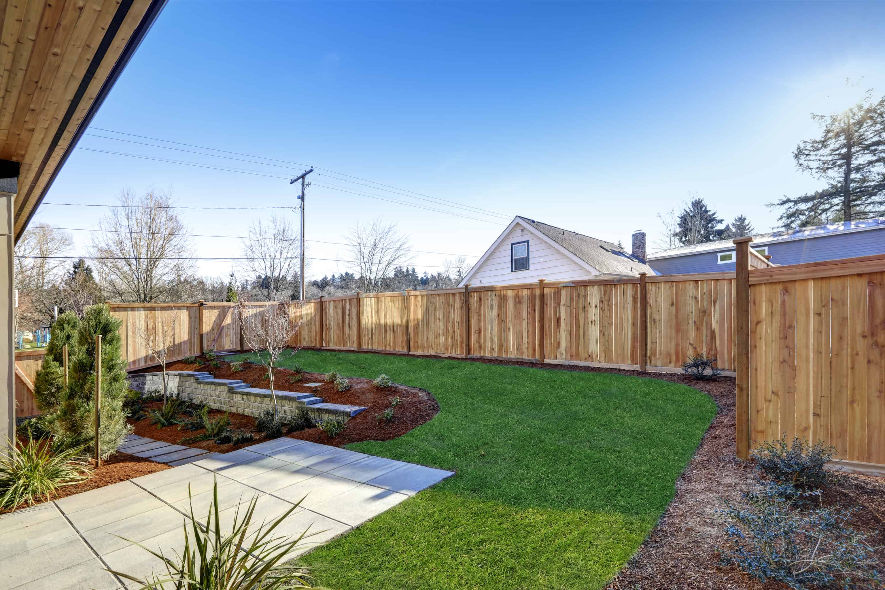 Sloped backyard surrounded by wooden fence.