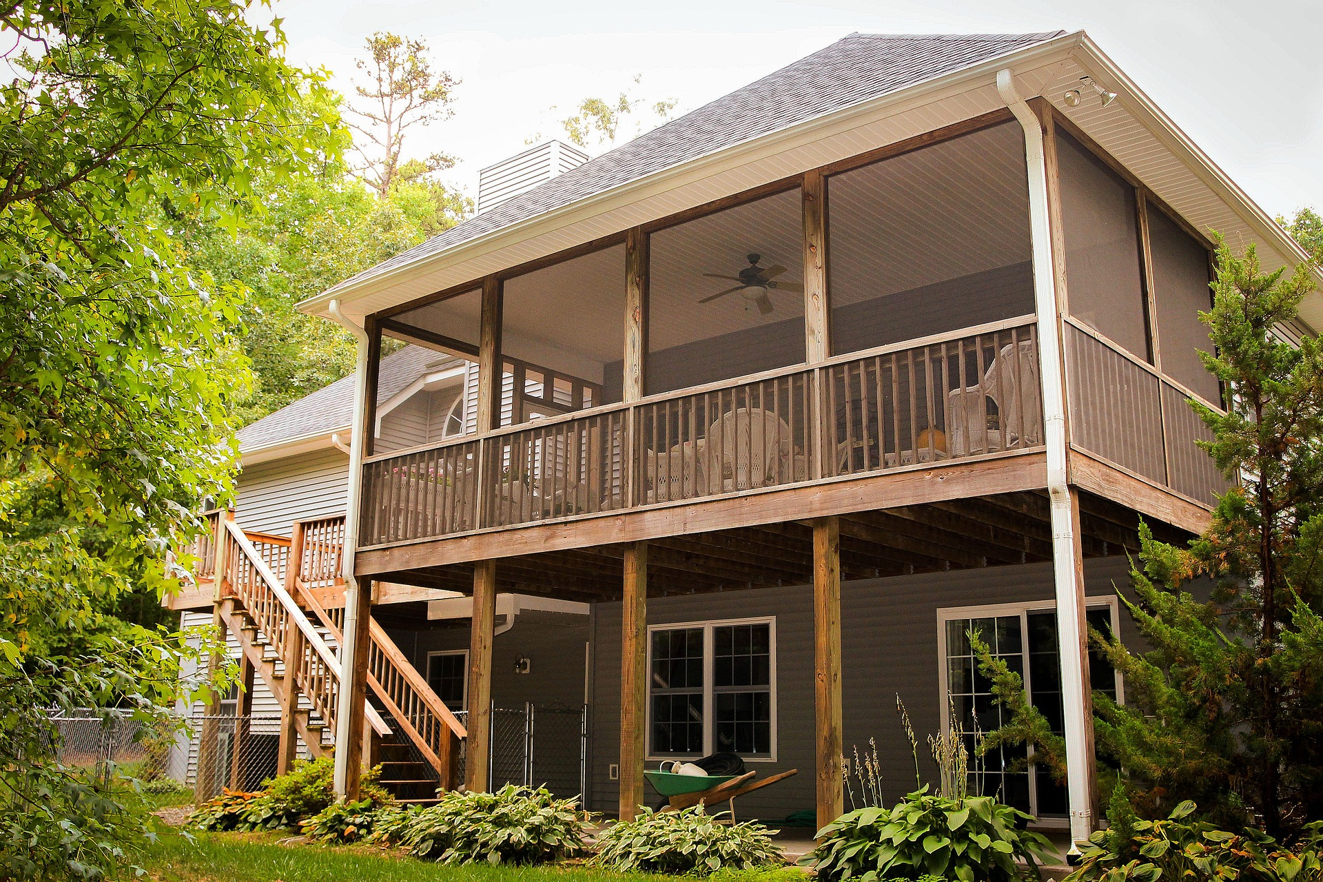 An outside deck with matching wood paneling for the floor and fencing; a patio set with a table and four chairs