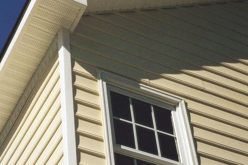 Yellow vinyl siding on a home with a paneled window.